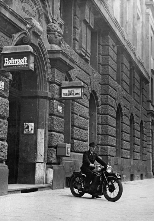 """Postbote auf BMW-Motorrad vor Haupttelegrafenamt, Schild """"Rohrpost"""" neben Eingang"""