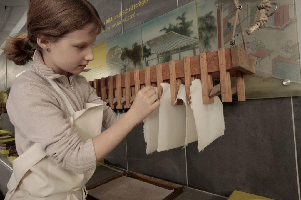 Mädchen beim Papierschöpfen im Technikmuseum Berlin