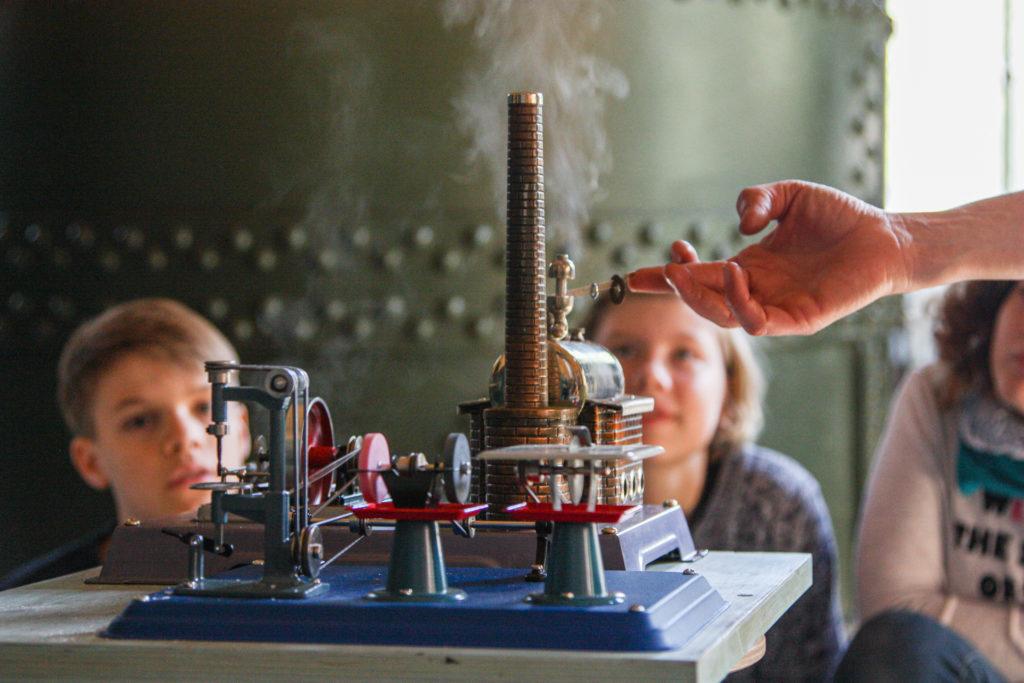 Kinder bestaunen Modell einer Dampfmaschine im Ökowerk Berlin zur JuniorRoute